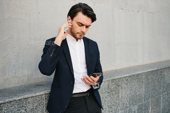 Young stylish man in classic suit with wireless earphones thoughtfully using cellphone - Stock Photo - Images