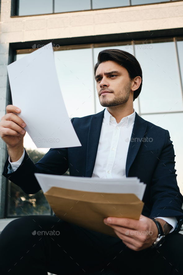 Handsome man in classic jacket sitting outdoor thoughtfully reading documents over glass building - Stock Photo - Images