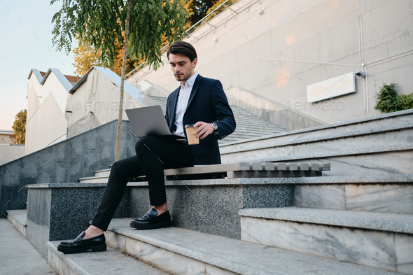 Young stylish man in classic suit sitting on bench drinking coffee thoughtfully working on laptop - Stock Photo - Images