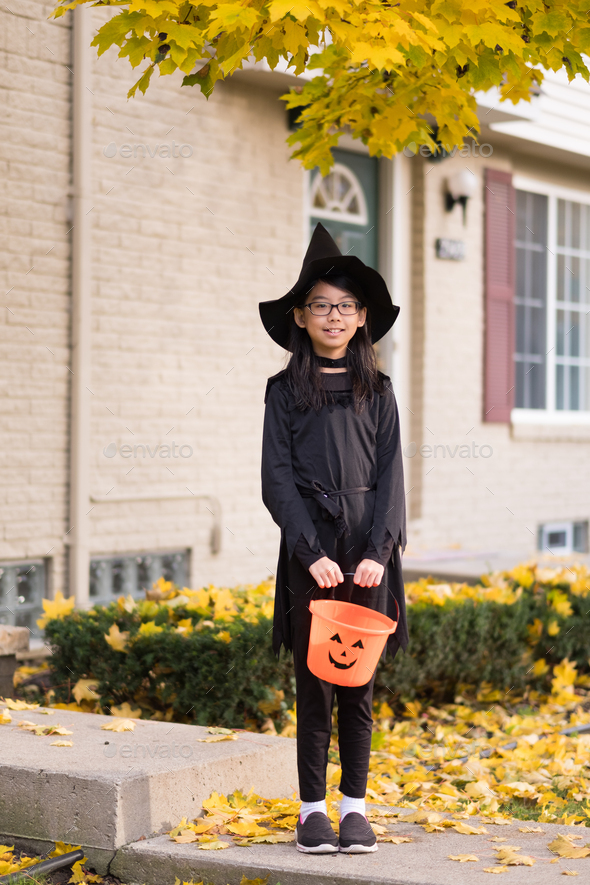 Portrait of little asian girl in witch costume - Stock Photo - Images