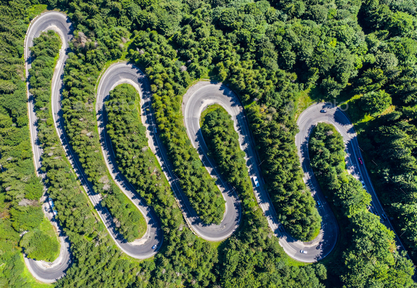 Aerial top view of a winding road in green forest by drone - Stock Photo - Images
