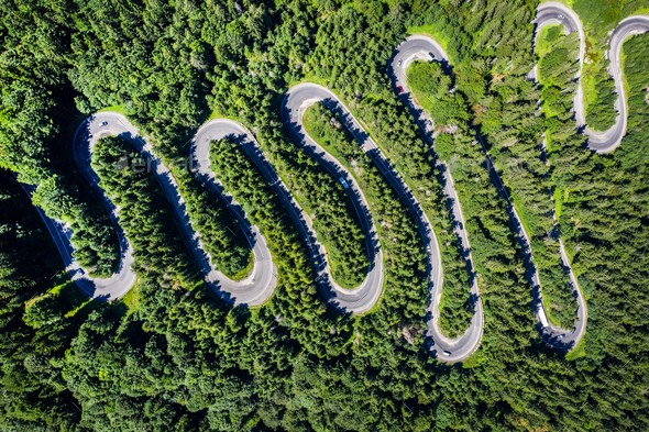 Aerial view of a winding road in green forest by drone - Stock Photo - Images
