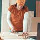 Female carpenter tape measuring picture frame in workshop - PhotoDune Item for Sale