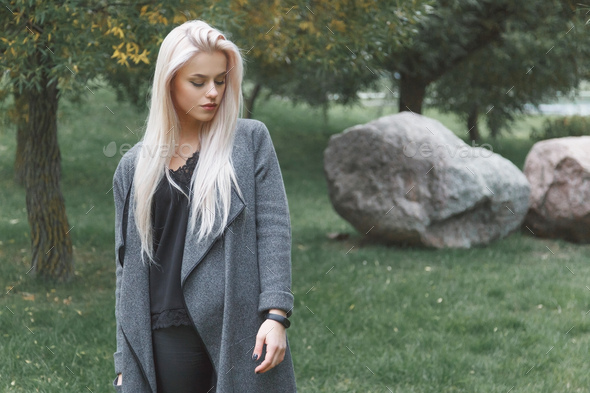 Young blondhair woman in a gray coat with smart bracelet standing outdoor. - Stock Photo - Images