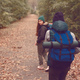 Girlfriends travelers with backpacks went hiking in the woods. - PhotoDune Item for Sale