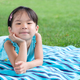 Little toddler girl laying on towel in the grass on a summer day - PhotoDune Item for Sale