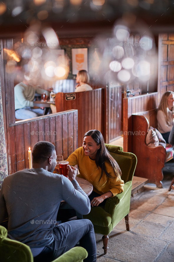 Couple Meeting For Lunchtime Drinks In Traditional English Pub Making A Toast - Stock Photo - Images