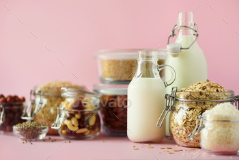 Glass bottles of vegan plant milk and almonds, nuts, coconut, hemp seed milk on pink background