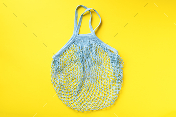 Reusable net bag or mesh shopper on yellow paper background. Zero waste, plastic free concept. Top