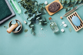 Soap, eucalyptus, towels, massage brush, salt, aroma oil and other spa objects on green background
