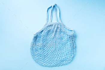 Reusable net bag or mesh shopper on blue paper background. Zero waste, plastic free concept. Top