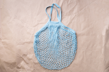 Reusable net bag or mesh shopper on craft paper background. Zero waste, plastic free concept. Top