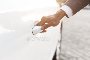 Hand on handle. Male hand in formalwear opening car door