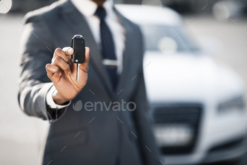 Car sale and rental concept. Businessman showing car key