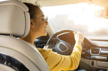 Happy afro woman driving her new car