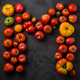 Letter M made with ripe tomatoes on a black background, creative flat lay healthy food concept - PhotoDune Item for Sale