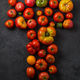 Letter T made with ripe tomatoes on a black background, creative flat lay healthy food concept - PhotoDune Item for Sale