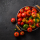 Ripe tomatoes in a pan on black stone background, copy space - PhotoDune Item for Sale