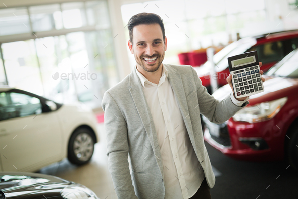 Car salesman calculating a price at the dealership office - Stock Photo - Images