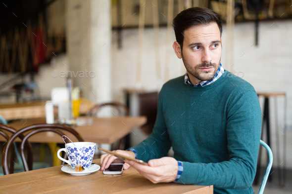 Portrait of young attractive man using tablet - Stock Photo - Images