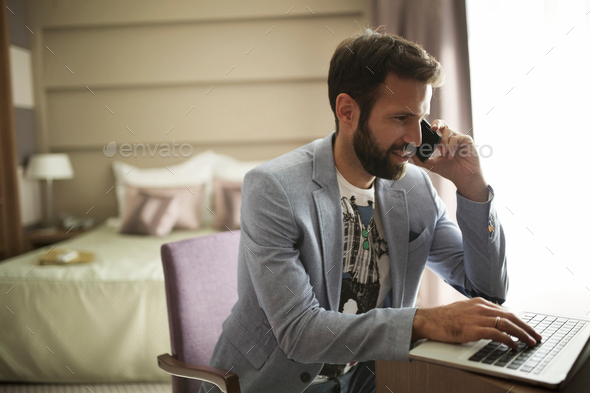Picture of young successful businessman talking on phone and using laptop - Stock Photo - Images