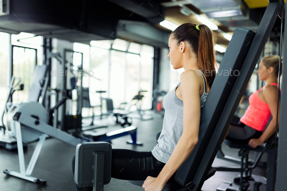 Young women exercising on machine in gym - Stock Photo - Images