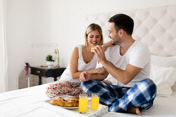 Romantic young couple having breakfast in bed - Stock Photo - Images