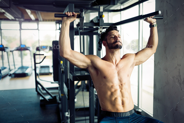 Young bodybuilder training in gym on machine - Stock Photo - Images