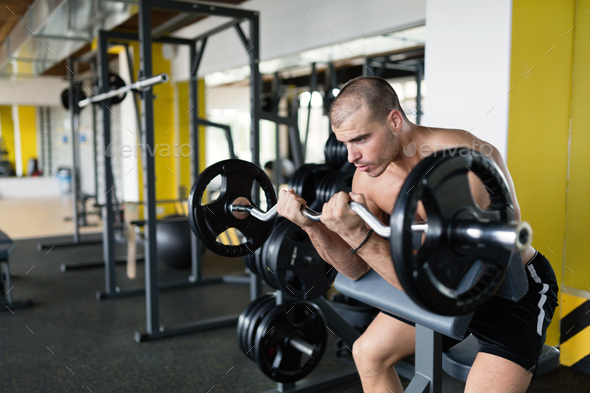 Athlete muscular bodybuilder in gym training biceps - Stock Photo - Images