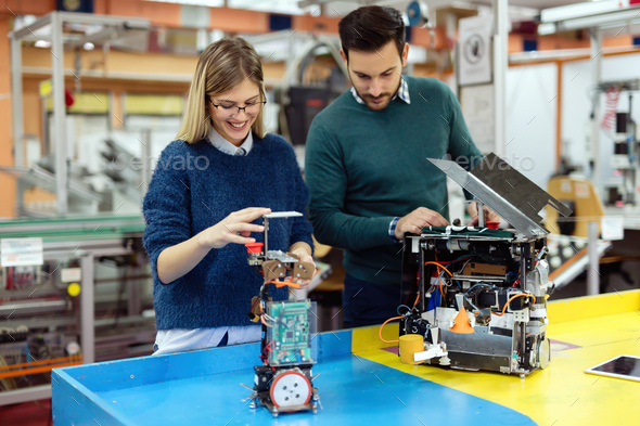 Young students of robotics preparing robot for testing - Stock Photo - Images