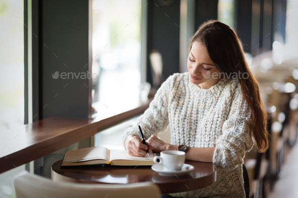 Beautiful woman sitting in restaurant and writing - Stock Photo - Images