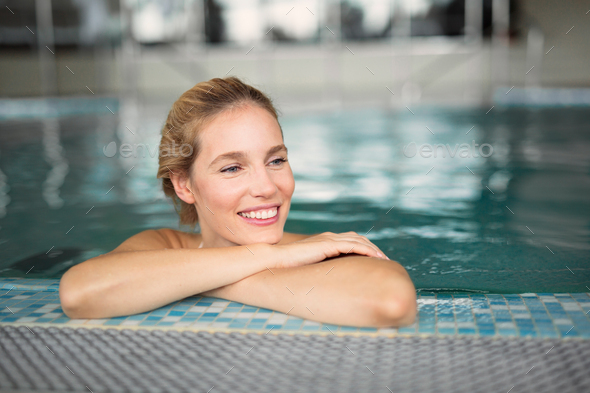 Portrait of beautiful woman relaxing in swimming pool - Stock Photo - Images