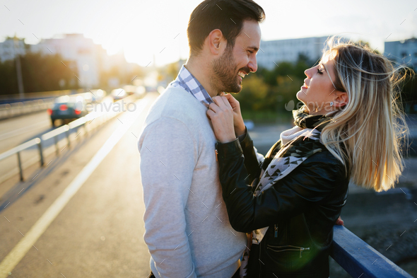 Happy young attractive couple hugging on bridge - Stock Photo - Images