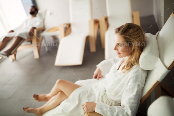 Portrait of beautiful blonde woman relaxing on chair - Stock Photo - Images
