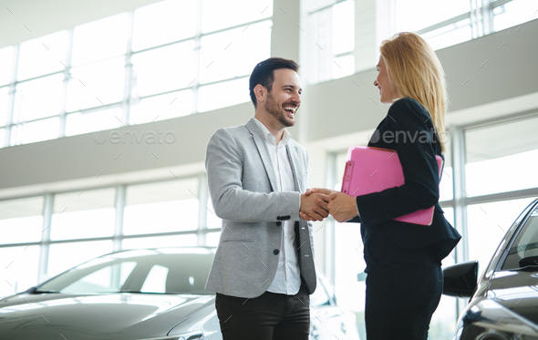 Professional salesperson during work with customer at car dealership - Stock Photo - Images