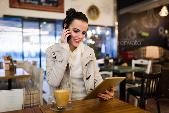 Attractive young woman using tablet in cafe - Stock Photo - Images