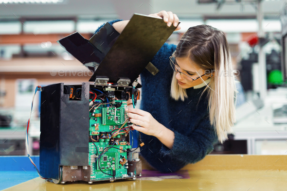 Young woman engineer working on robotics project - Stock Photo - Images