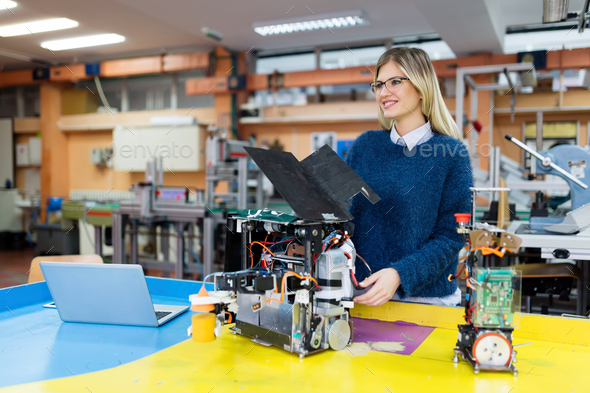Young beautiful female engineer testing robot in workshop - Stock Photo - Images
