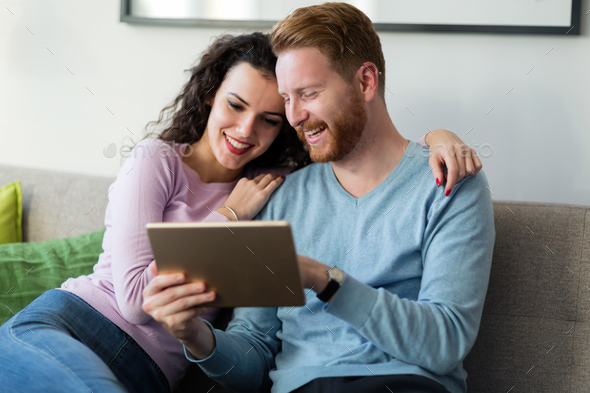 Young couple using digital tablet at home - Stock Photo - Images
