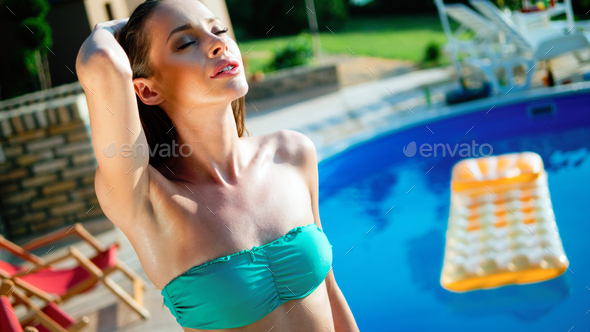 Woman relaxing and sun tanning by the swimming pool - Stock Photo - Images
