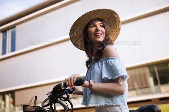 Portrait of beautiful young woman enjoying time on bicycle - Stock Photo - Images