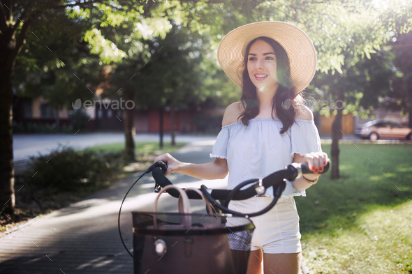 Portrait of beautiful woman enjoying time on bicycle - Stock Photo - Images