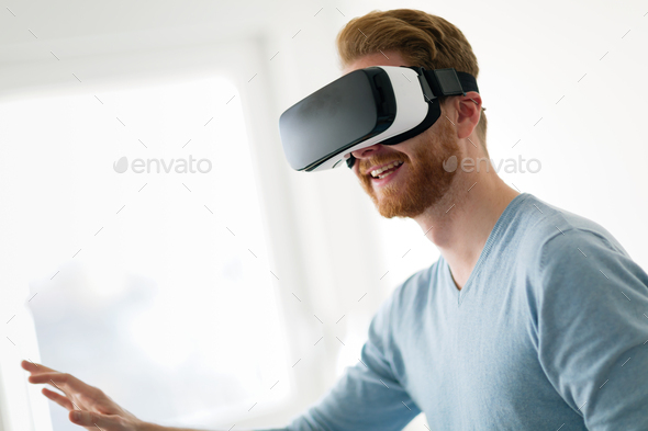 Man wearing virtual reality headset at home - Stock Photo - Images