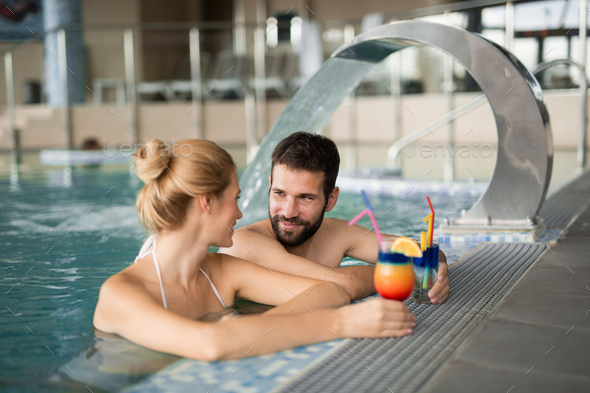 Cheerful happy couple relaxing in swimming pool - Stock Photo - Images