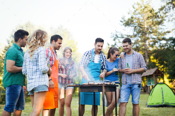 Friends enjoying bbq party and smiling in nature - Stock Photo - Images