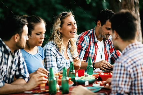 Group of happy people eating food outdoors - Stock Photo - Images