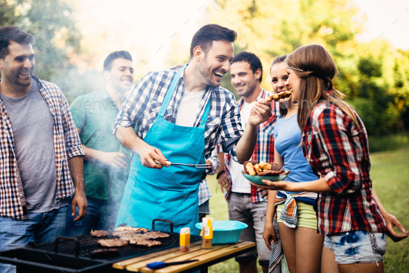 Happy friends enjoying barbecue party - Stock Photo - Images