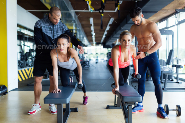 Young women in gym doing exercises with trainers - Stock Photo - Images