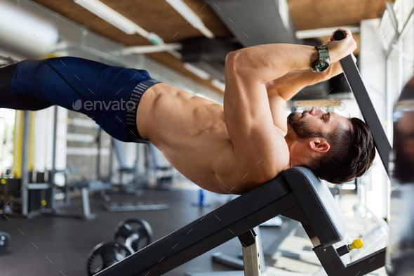 Young handsome man doing exercise for abdominal muscles - Stock Photo - Images