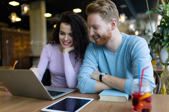 Happy couple spending time at coffee shop working on laptop - Stock Photo - Images